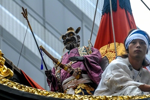 iwato yama izanagi no mikoto deity statue on roof with man gion festival kyoto japan
